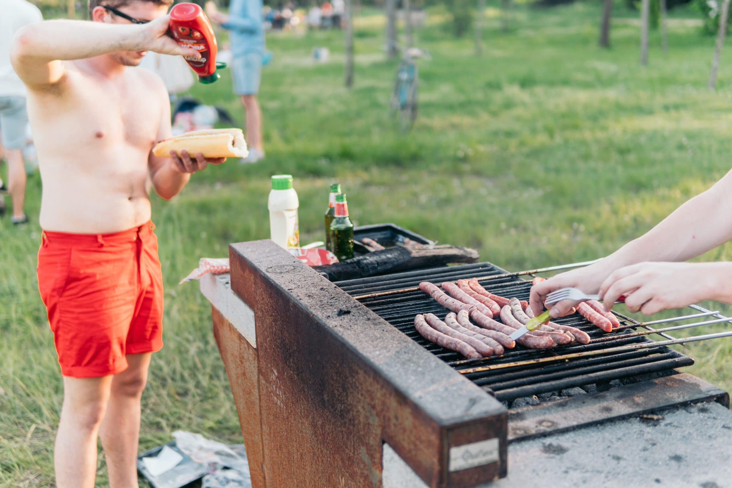 man wearing red shorts standing at grill putting ketchup on hotdog