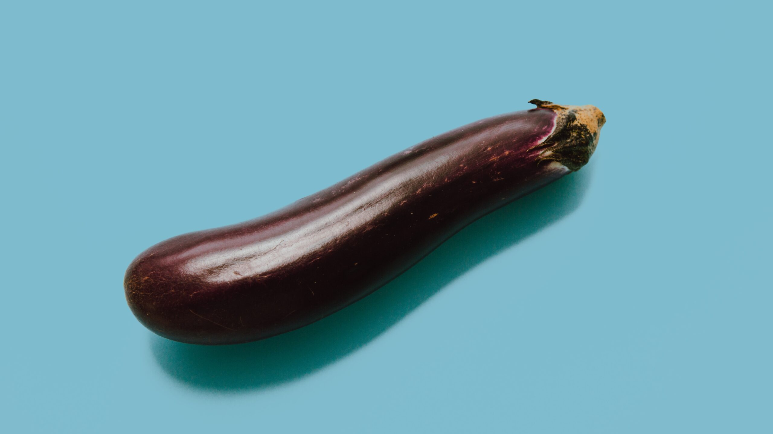brown eggplant on teal surface