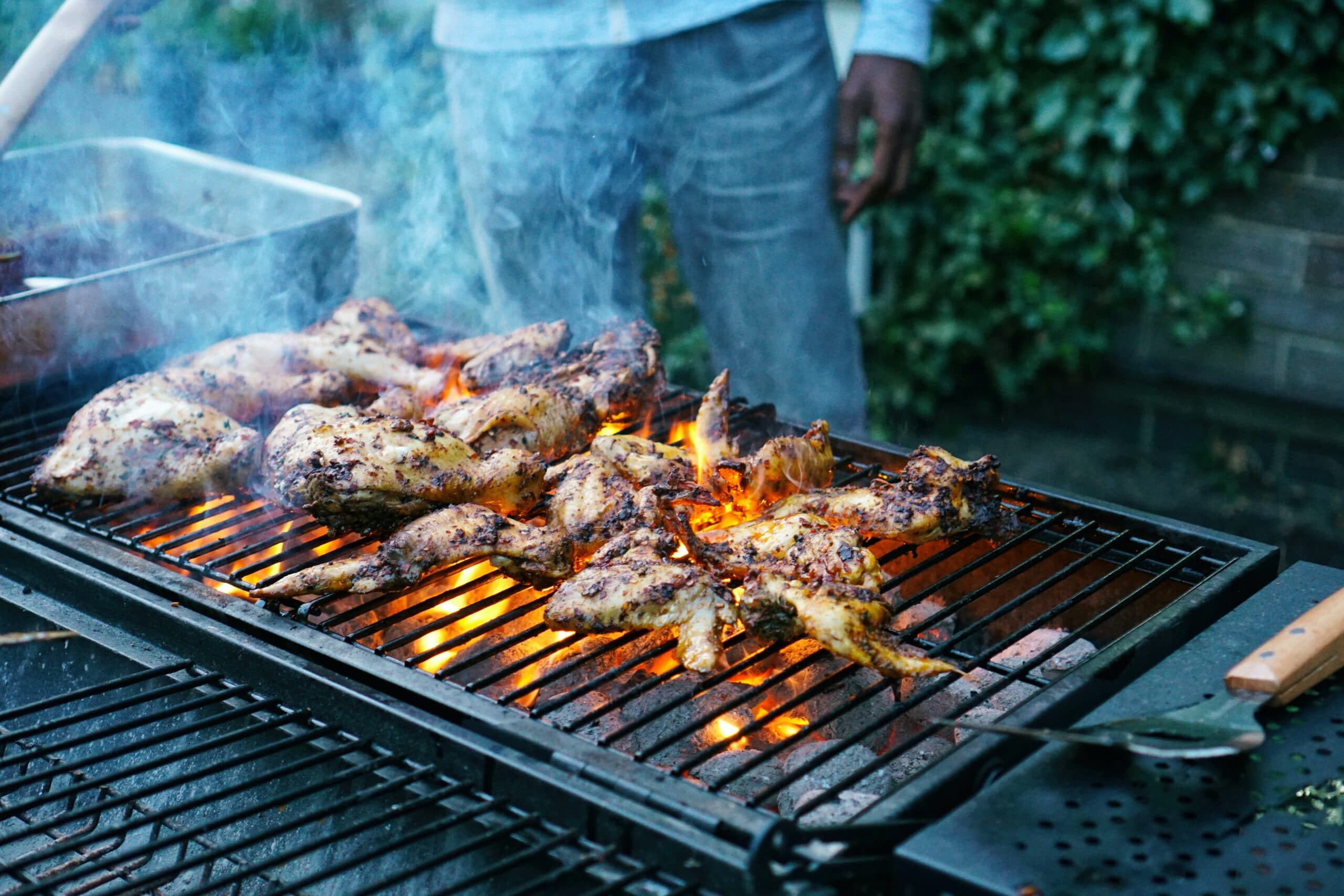 unknown person grilling chicken meat outdoors