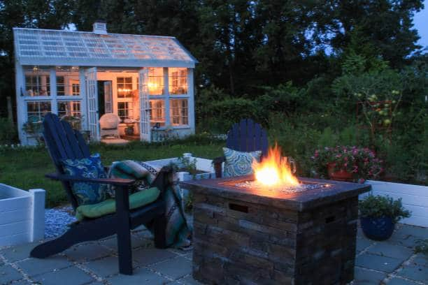 Beautiful garden with fire pit andirondack chairs and greenhouse