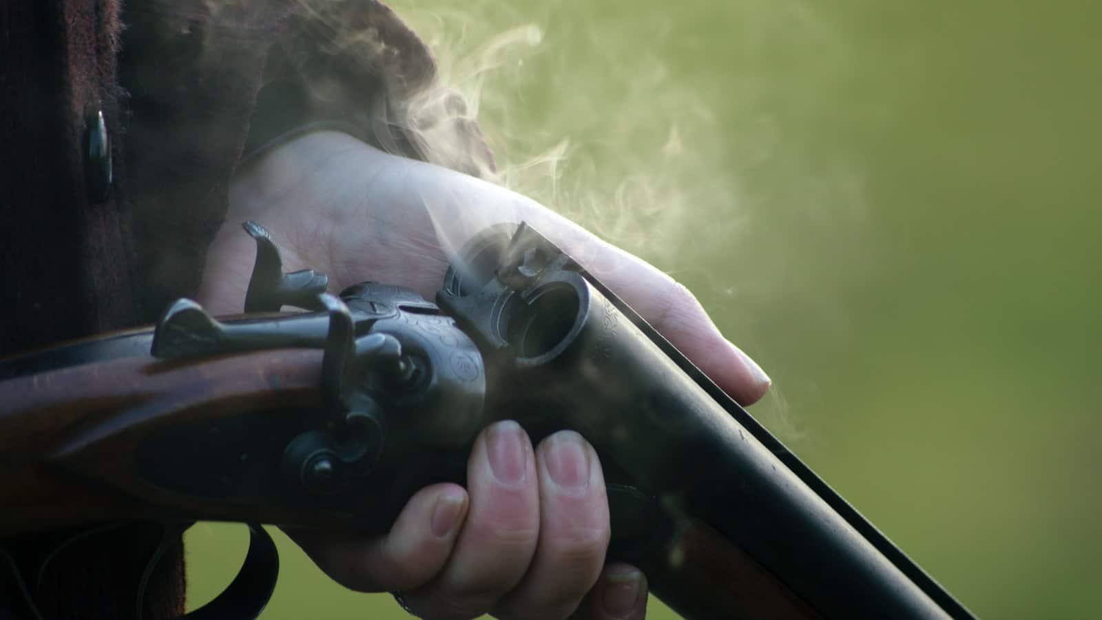 person holding shotgun