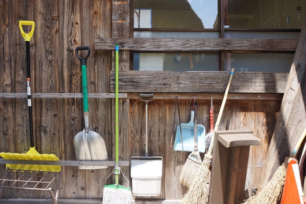 white plastic bucket beside brown wooden wall