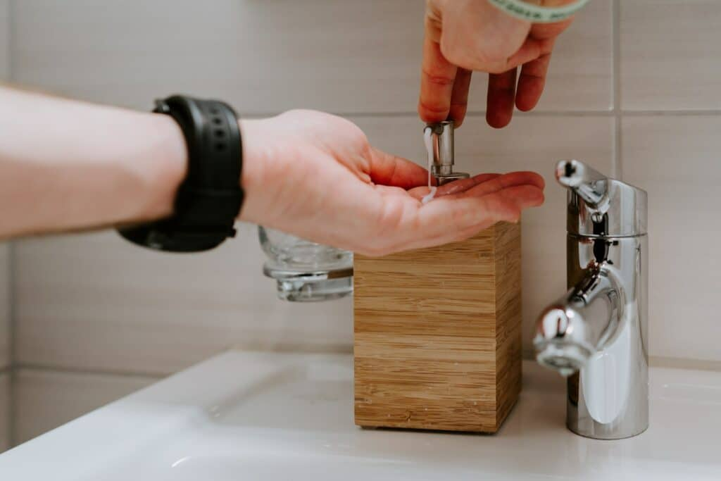person holding silver faucet in sink