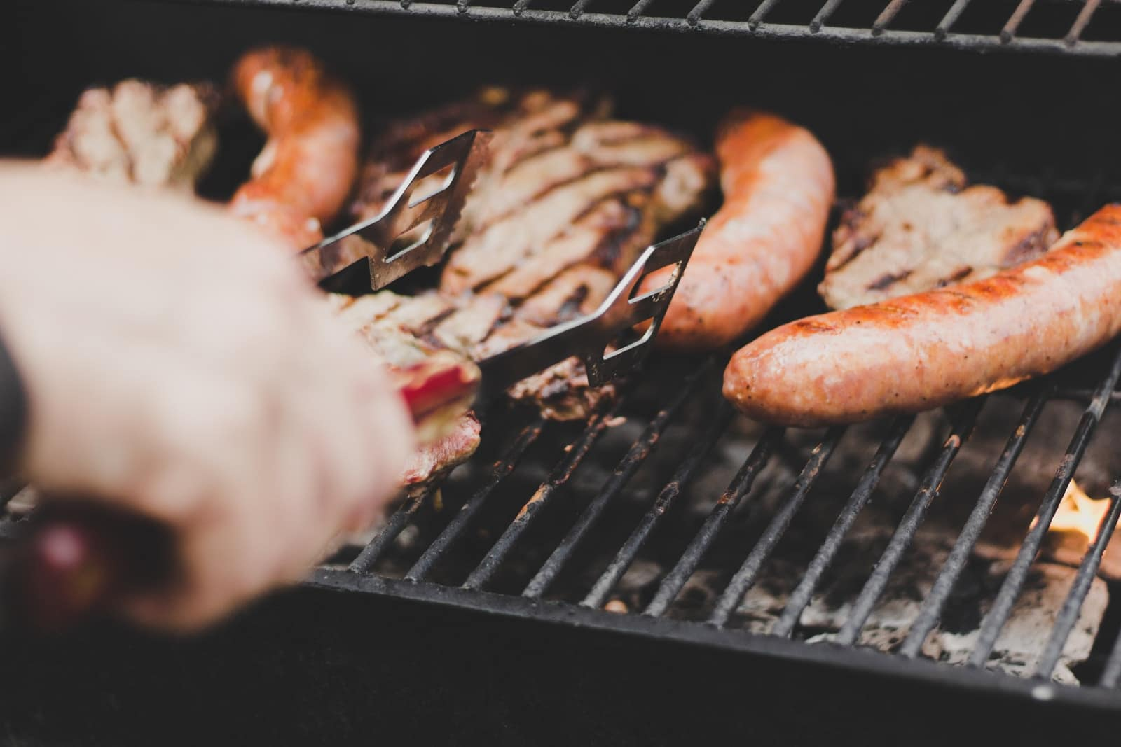 person grilling sausage and meat